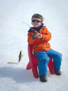 A little boy sits on the ice with a caught fish