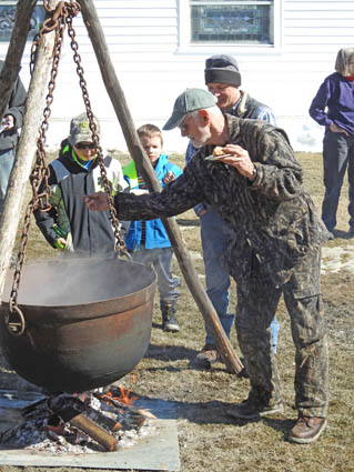 Courtesy Middletown Springs Historical Society Fred Bradley demonstrates old-fashioned maple sugaring in a cast iron kettle over an open fire during Maple Festival in Middletown Springs.